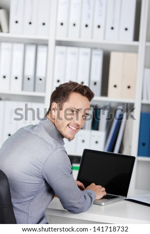 Portrait of a smiling young businessman using laptop at office desk - stock photo