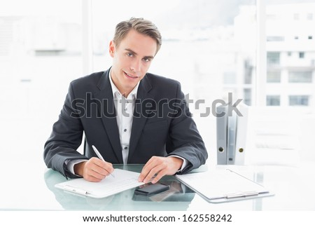 Portrait of a smiling young businessman writing documents at office desk