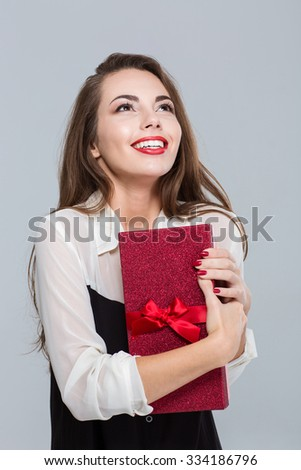 Portrait of a smiling young businesswoman holding gift box and looking up over gray background - stock photo