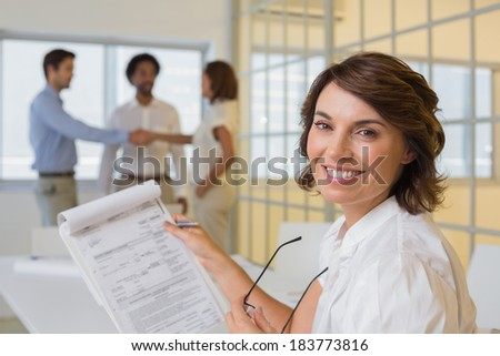 Portrait of a smiling young businesswoman with colleagues shaking hands in background at the office - stock photo