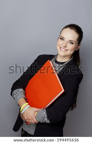 Portrait of a smiling young businesswoman, with long brunette hair, on gray studio background, holding a closed red book or album in her hands - stock photo