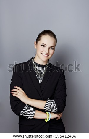 Portrait of a smiling young businesswoman, with long brunette hair, on gray studio background, wearing black blazer over striped top - stock photo