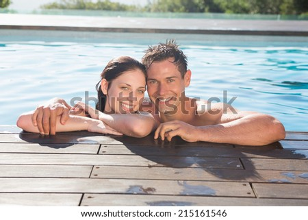 Portrait of a smiling young couple in swimming pool on a sunny day - stock photo