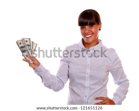 Portrait of a smiling young female holding cash money standing over white background - stock photo