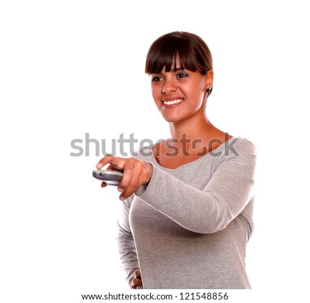 Portrait of a smiling young female using a tv remote against white background - stock photo