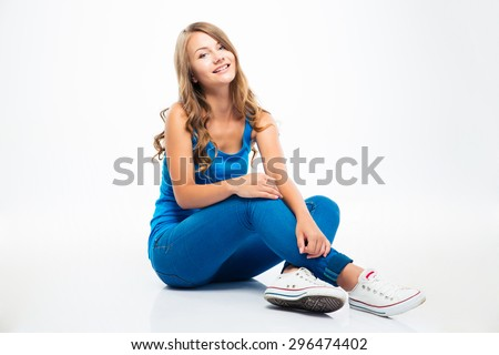 Portrait of a smiling young girl sitting on the floor isolated on a white background - stock photo