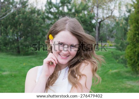portrait of a smiling young girl with hand on her face, with chamomiles  in her hair on the nature background - stock photo