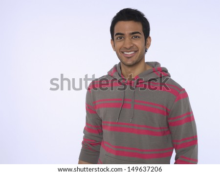 Portrait of a smiling young Indian man against purple background - stock photo