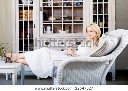 Portrait of a smiling young lady sitting on sofa in house - stock photo