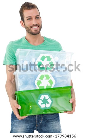 Portrait of a smiling young man carrying recycle containers over white background