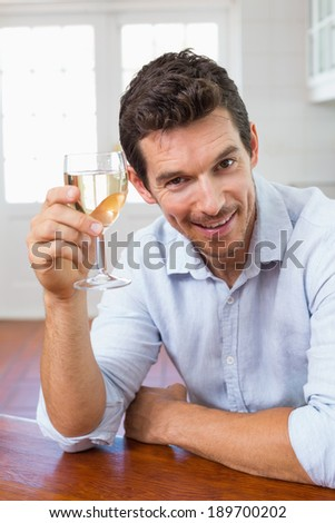 Portrait of a smiling young man holding a wine glass at home - stock photo