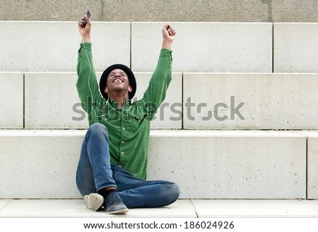 Portrait of a smiling young man listening to music with earphones outdoors with arms raised - stock photo