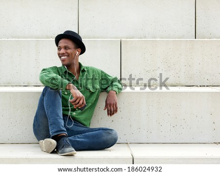 Portrait of a smiling young man relaxing outdoors listening to music on earphones - stock photo