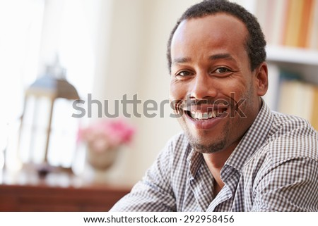 Portrait of�¿a smiling young man sitting in a room - stock photo