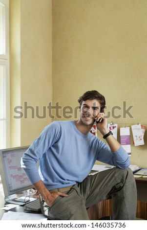 Portrait of a smiling young man using cellphone by computer in the office - stock photo