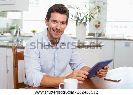 Portrait of a smiling young man using digital tablet at home - stock photo