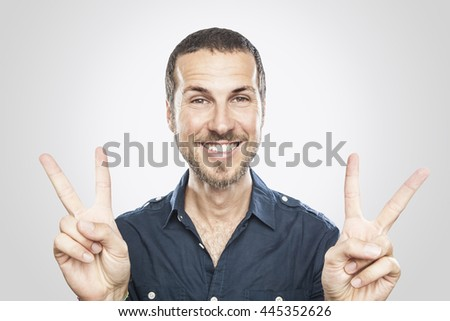 portrait of a smiling young man, victory sign