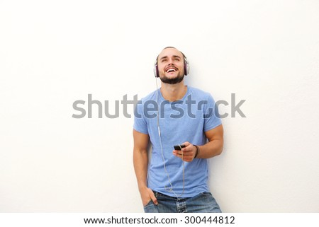 Portrait of a smiling young man with mobile phone and headphones - stock photo