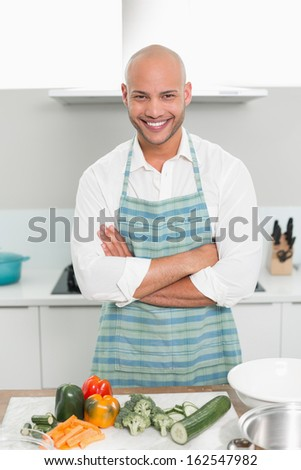Portrait of a smiling young man with vegetables standing in the kitchen at home - stock photo