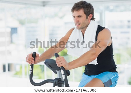 Portrait of a smiling young man working out at class in a bright gym