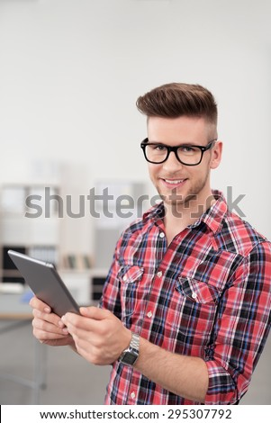 Portrait of a Smiling Young Office Guy in Casual Outfit, Holding a Tablet Computer and Looking at the Camera. - stock photo
