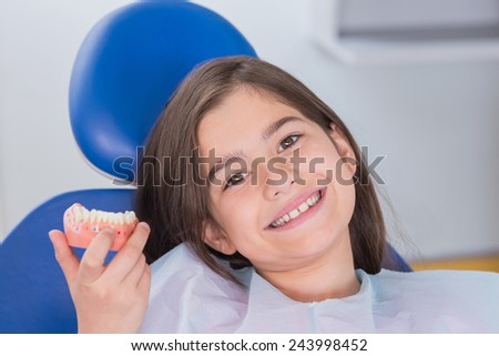 Portrait of a smiling young patient showing model in dental clinic - stock photo
