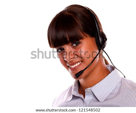 Portrait of a smiling young secretary using earphone looking at you on isolated background - stock photo