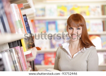 portrait of a smiling young  student in a library - stock photo