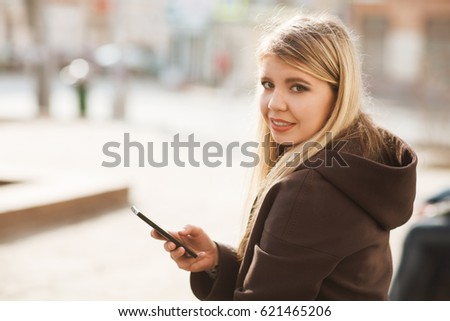 portrait of a smiling Young stylish woman with mobile phone to go in a city street in the  morning