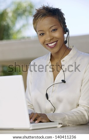 Portrait of a smiling young support phone operator in headset with laptop at patio