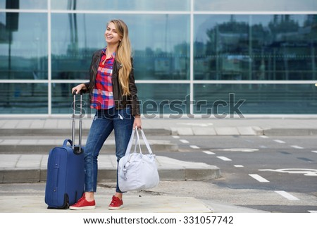 Portrait of a smiling young travel woman standing outside with bags