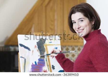 Portrait of a smiling young woman artist painting. - stock photo