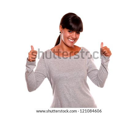 Portrait of a smiling young woman celebrating a victory while is looking at you standing on isolated background - stock photo
