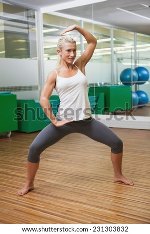 Portrait of a smiling young woman doing power fitness exercise at yoga class - stock photo