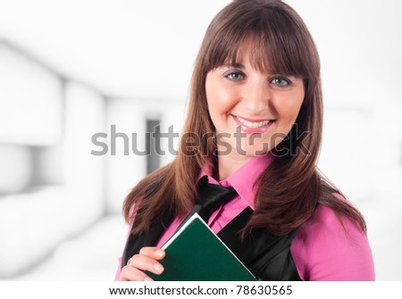 Portrait of a smiling young woman holding a book - stock photo