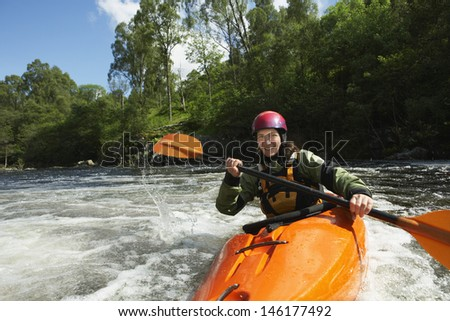 Portrait of a smiling young woman kayaking in the river - stock photo