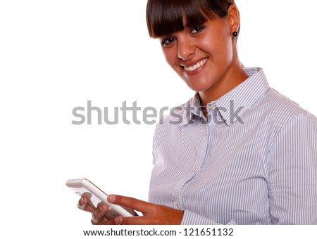 Portrait of a smiling young woman looking at you with cellphone against white background - stock photo