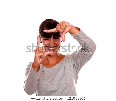 Portrait of a smiling young woman making frame shape with her hand on grey dress standing on isolated background - stock photo