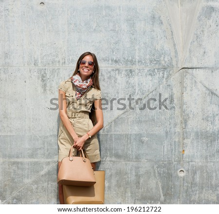 Portrait of a smiling young woman posing with bags outdoors - stock photo