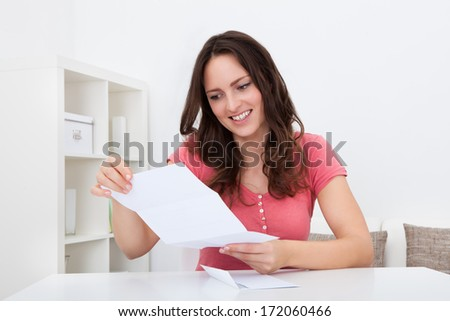 Portrait Of A Smiling Young Woman Reading Documents - stock photo