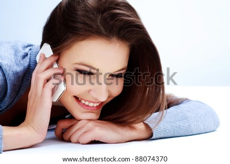 Portrait of a smiling young woman talking on mobile phone - stock photo
