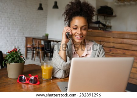 Portrait of a smiling young woman talking on mobile phone and working on laptop at home - stock photo