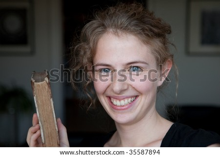 portrait of a smiling young woman with an old book in her hand, before modern minimalistic interior design fo a library (natural beauty) - stock photo