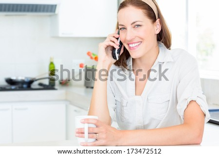Portrait of a smiling young woman with coffee cup using mobile phone in the kitchen at home