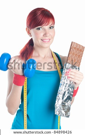 Portrait of a smiling young woman with dumbbell in one hand and a bar of chocolate in another, isolated on white, studio shot - stock photo