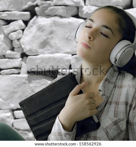 Portrait of a smiling young woman with headphone listening music while is browsing the internet on laptop computer  - stock photo