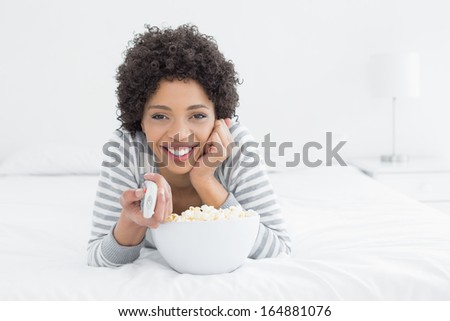 Portrait of a smiling young woman with remote control and popcorn bowl lying in bed at home - stock photo