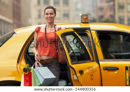 Portrait of a smiling young woman with shopping bags exiting yellow taxi - stock photo