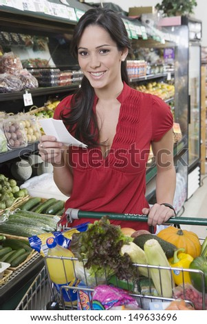 Portrait of a smiling young woman with shopping in supermarket - stock photo