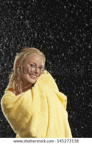 Portrait of a smiling young woman wrapped in yellow towel in rain